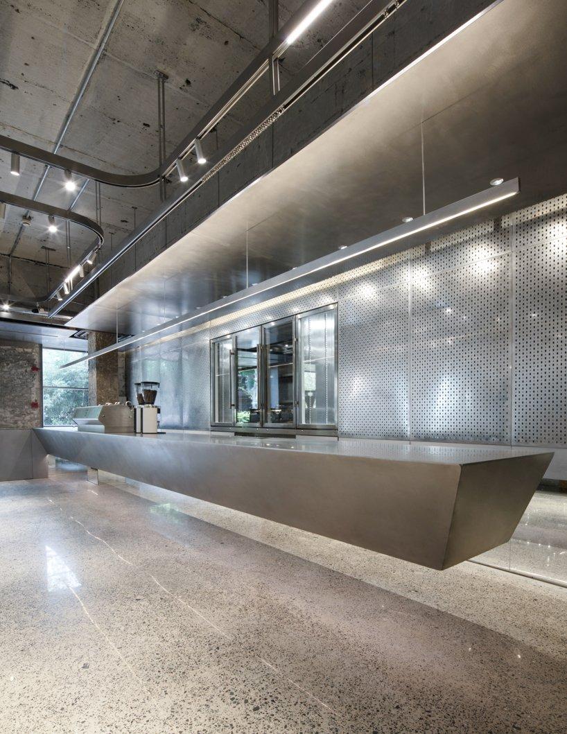 comptoirs en acier, murs en béton + cloisons rideaux métalliques réalisent le café 'basdban' à shanghai