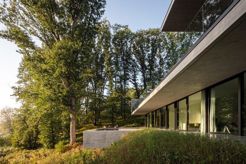 résidence en béton linéaire par les architectes govaert & vanhoutte se fond dans la forêt belge
