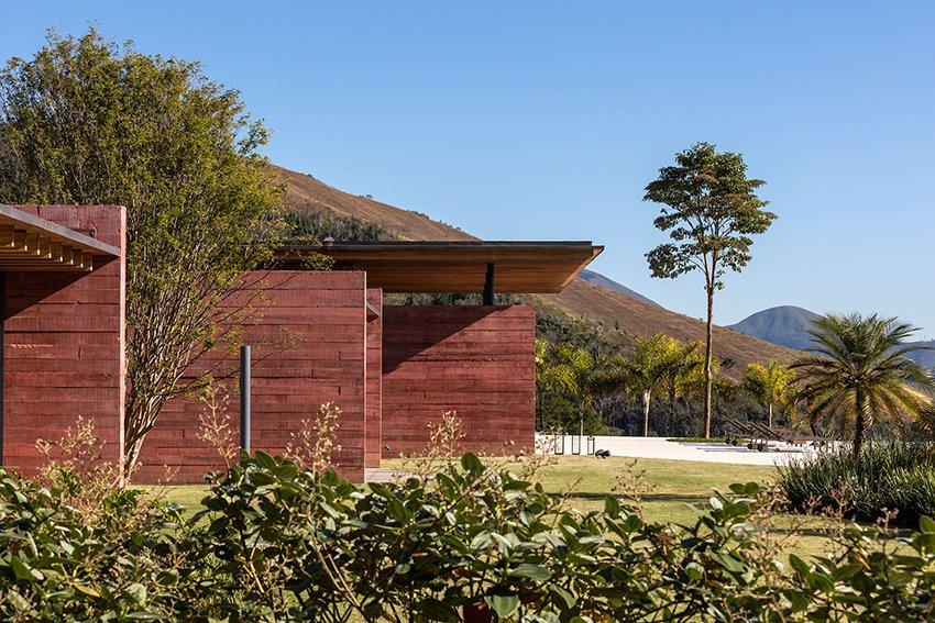 des murs teintés en terre cuite ornent cette maison de week-end au sommet d'une colline au Brésil par bernardes arquitetura