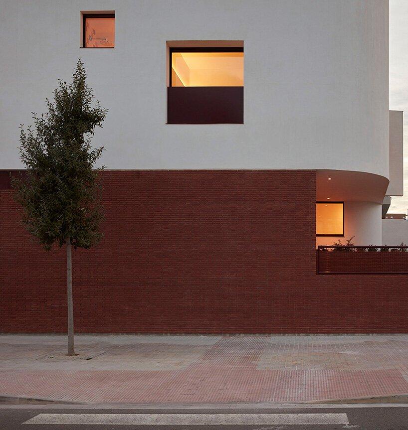 Le socle en brique contraste avec la masse courbée en béton dans la casa AA d'Horma Estudio en Espagne