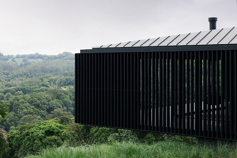 Le bureau de l'édition ancre une résidence en béton noir avec des ouvertures stratégiques au sommet d'une colline australienne