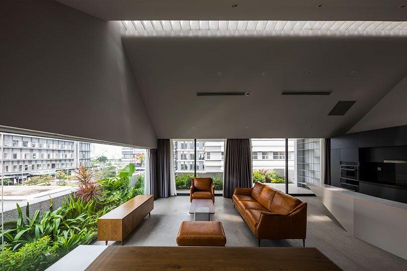 23o5studio interrompt un bloc de banlieue au vietnam avec une maison en béton J14 en pente