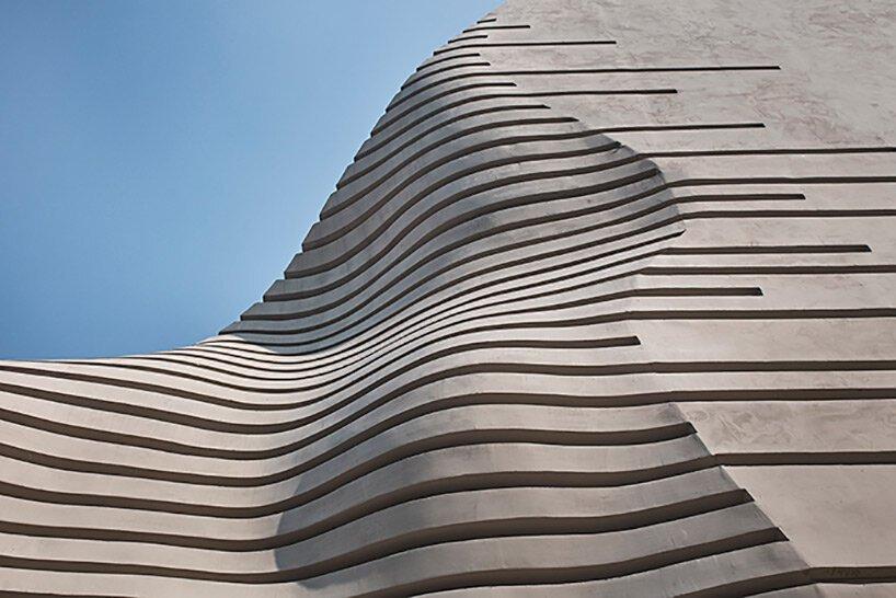spa pyramidoïde en béton avec diverses découpes se démarque dans le tissu urbain dense de Séoul